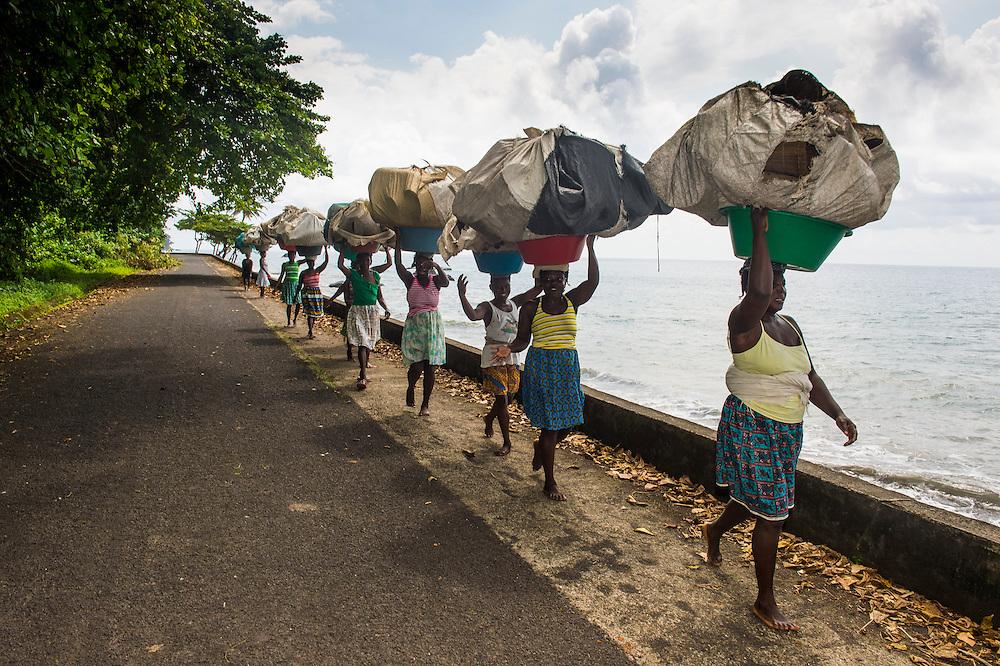Frauen mit riesigen Ballen auf den Köpfen auf dem Weg nach Hause