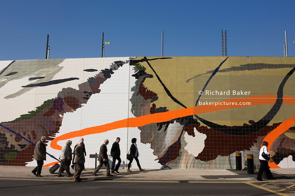 Visitors to the 2012 Stratford Olympic Park walk past an artwork mural.