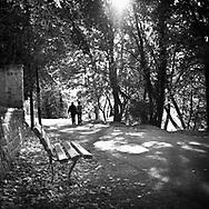 A couple walk the path along the Seine River in Croissy-sur-Seine, France.   Aspect Ratio 1w x 1h