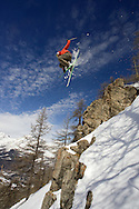 Skier jumping off rock on mountainside, Serre Chevalier, France