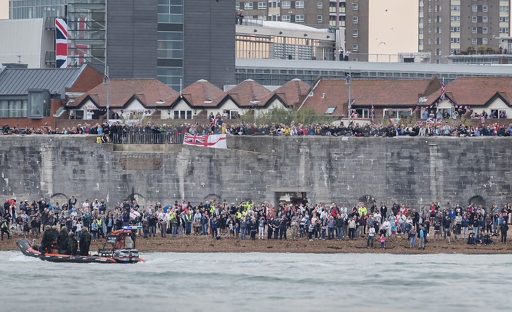 © Licensed to London News Pictures. 16/08/2017. Portsmouth, UK. Crowds watch from the shore as the Royal Navy's new aircraft carrier HMS Queen Elizabeth enters her home port of Portsmouth for the first time. The new ship at 65,000 tonnes is the biggest warship ever built in the UK. Photo credit: Peter Macdiarmid/LNP
