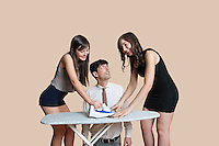 Shocked man looking at young females ironing tie over colored background