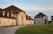 Berniers Ouest (left), saltworkers accommodations, and the Pavillon des Commis (right), with Palladian facade, housing offices and accommodation for the Saltworks accountants and foremen, part of the Royal Saltworks or Saline Royale, begun 1775 in Neoclassical style by architect Claude Nicolas Ledoux, 1736-1806, at Arc-et-Senans, Doubs, Bourgogne-Franche-Comte, France. The site is designed in a semicircle, with the Director's House, 2 saltworks containing drying ovens, heating pots and salt stores, workers' accommodation and Director's stables. An Ideal City was also planned but never built. The site is listed as a UNESCO World Heritage site. Picture by Manuel Cohen