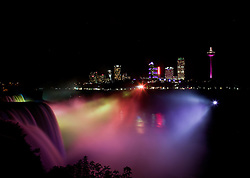 American and Bridal Veil falls at night, with the city of Niagara Falls, Canada, in background.