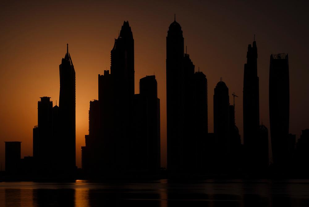 UNITED ARAB EMIRATES, DUBAI - CIRCA JANUARY 2017: Silhouette of the Dubai Marina cityscape and skyscrapers as seen from Palm Jumeirah at sunrise.