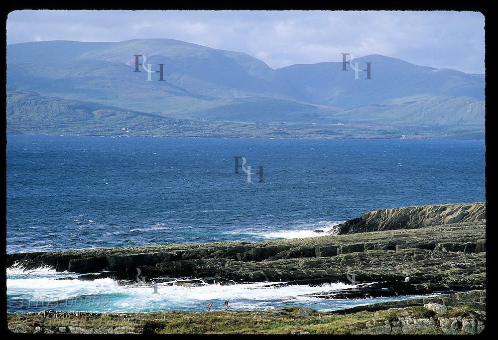 Two backpackers hike Beara Way at Kilcatherine dwarfed by mountainous Iveragh Peninsula and ocean bay; Beara Peninsula, Ireland.