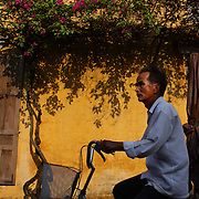 A street scene in Hoi An, Vietnam as a Vietnamese man rides past a bright yellow wall with hanging summer flowers. Hoi An is an ancient town and an exceptionally well-preserved example of a South-East Asian trading port dating from the 15th century. Hoi An is now a major tourist attraction because of its history. Hoi An, Vietnam. 5th March 2012. Photo Tim Clayton