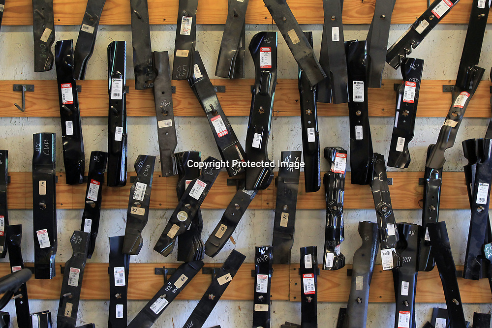 A wall in the service area of Turf Pros is devoted to holding a stock of different types and sizes of lawn mower blades.