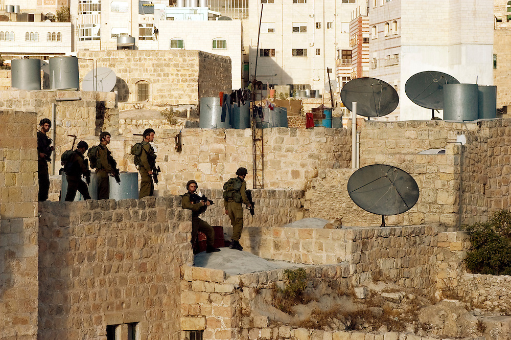 Israeli special forces search the rooftops of Palestinian homes surrounding the Jewish community in Hebron. Approximately 600 Jewish settlers live in the historic center of the city which has a Palestinian population of more than 160,000..Hebron, Israel. 08/11/2007.Photo © J.B. Russell/Blue Press