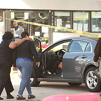 A police official lifts crime scene tape for family members who got into a damaged car outside an Exxon gas station at 2330 Ashley Phosphate Road in North Charleston where a man was fatally shot Friday afternoon. (ANDREW KNAPP/STAFF)