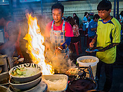 24 NOVEMBER 2015 - BANGKOK, THAILAND:  A street food vendor makes oyster omelets at the Wat Saket temple fair. Wat Saket is on a man-made hill in the historic section of Bangkok. The temple has golden spire that is 260 feet high which was the highest point in Bangkok for more than 100 years. The temple construction began in the 1800s in the reign of King Rama III and was completed in the reign of King Rama IV. The annual temple fair is held on the 12th lunar month, for nine days around the November full moon. During the fair a red cloth (reminiscent of a monk's robe) is placed around the Golden Mount while the temple grounds hosts Thai traditional theatre, food stalls and traditional shows.       PHOTO BY JACK KURTZ