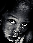 A hungry child in a refugee [IDP] camp in Kass, Darfur, August 2004, at the height of the conflict.  Thousands of people were crammed into the camp after fleeing from attacks by the Sudanese government-backed Janjaweed militia.  Conditions were poor and food was in short supply, but no-one dared leave for fear of further attacks.