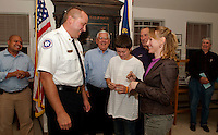 Gilford Fire Chief Stephen Carrier receives his pins from his son Ethan and wife Vickie after being sworn in at Gilford Town Hall Monday evening.  (Karen Bobotas/for the Laconia Daily Sun)