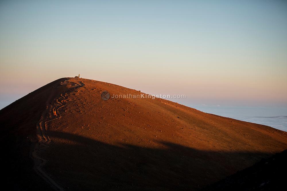 Two people walk to the 13,796 foot summit of Mauna Kea (Pu`u Wekiu), the tallest mountain in Hawaii, located on the Big Island.