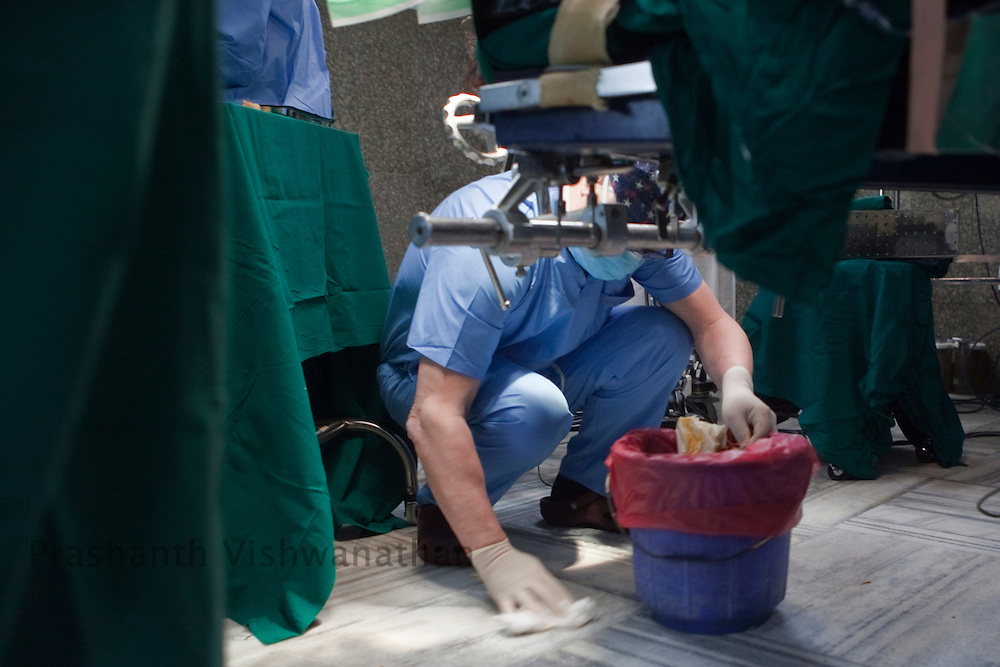 Professor, Juha Hernesniemi, cleans the floor off fallen cotton as he performs a neurosurgery in front of 170 Indian neurosurgeons at Bombay Hospital in Mumbai, India, on Sunday, April 17, 2011. Photographer: Prashanth Vishwanathan/HELSINGIN SANOMAT