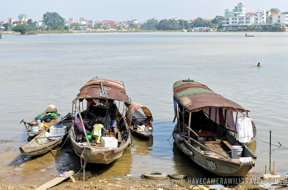 Boats moored up against the shore of the Perfume River near the Dong Ba market in Hue in central Vietnam. In the background, at right, a boy swims in the river.