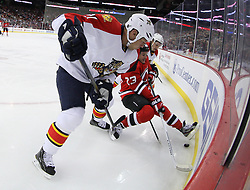 Feb 11; Newark, NJ, USA; Florida Panthers right wing Krys Barch (21) trips up New Jersey Devils right wing David Clarkson (23) while battling for the loose puck during the second period at the Prudential Center.