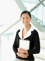 Smiling businesswoman standing holding notebook