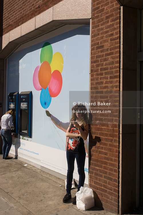 A young woman standing next to a Barclays Bank seemingly holds a bunch of multicoloured balloons.