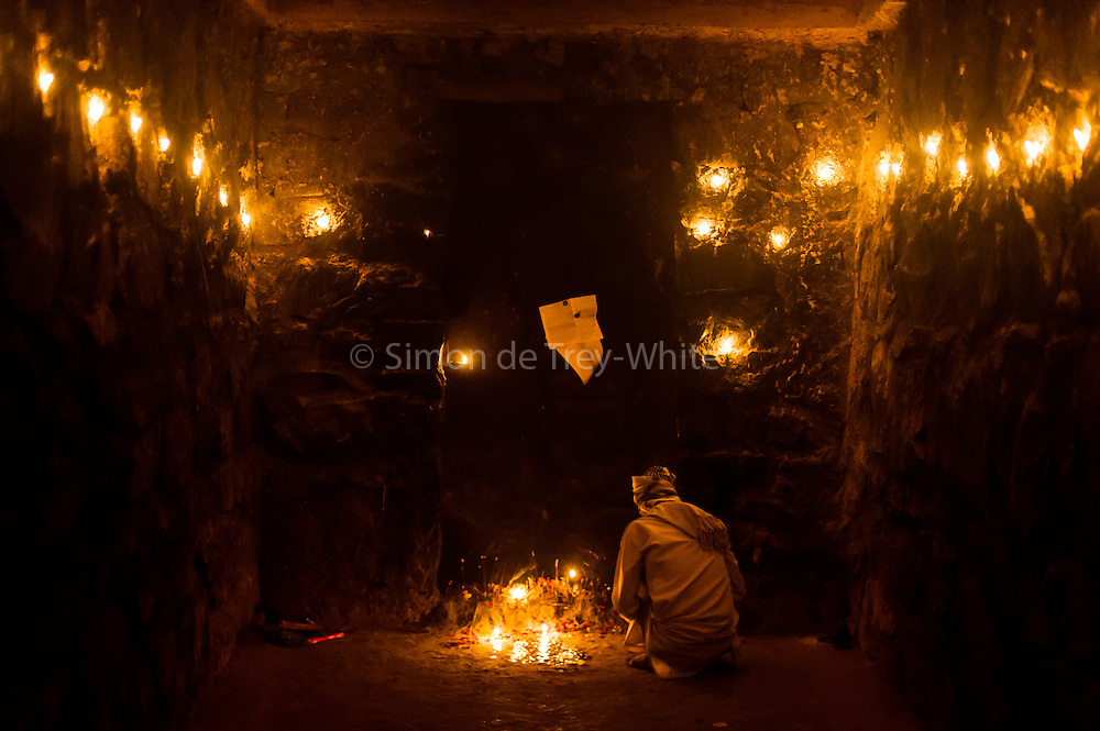 3rd December 2015, New Delhi, India.  A man at squats at a candlelit shrine dedicated to Djinn worship in the ruins of Feroz Shah Kotla in New Delhi, India on the 3rd December 2015<br /> <br /> PHOTOGRAPH BY AND COPYRIGHT OF SIMON DE TREY-WHITE a photographer in delhi<br /> + 91 98103 99809. Email: simon@simondetreywhite.com<br /> <br /> People have been coming to Firoz Shah Kotla to pray to and leave written notes and offerings for Djinns in the hopes of getting wishes granted since the late 1970's. Jinn, jann or djinn are supernatural creatures in Islamic mythology as well as pre-Islamic Arabian mythology. They are mentioned frequently in the Quran  and other Islamic texts and inhabit an unseen world called Djinnestan. In Islamic theology jinn are said to be creatures with free will, made from smokeless fire by Allah as humans were made of clay, among other things. According to the Quran, jinn have free will, and Iblīs abused this freedom in front of Allah by refusing to bow to Adam when Allah ordered angels and jinn to do so. For disobeying Allah, Iblīs was expelled from Paradise and called &quot;Shayṭān&quot; (Satan).They are usually invisible to humans, but humans do appear clearly to jinn, as they can possess them. Like humans, jinn will also be judged on the Day of Judgment and will be sent to Paradise or Hell according to their deeds. Feroz Shah Tughlaq (r. 1351&ndash;88), the Sultan of Delhi, established the fortified city of Ferozabad in 1354, as the new capital of the Delhi Sultanate, and included in it the site of the present Feroz Shah Kotla. Kotla literally means fortress or citadel.