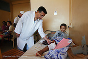 General Surgeon Dr RANDRIAMIHAJA Pierrot  examines the leg of a young boy waiting in the public ward to see if he will get on the surgery schedule at Antsirabe Hospital. Antsirabe Clinic Project sponsored by the Swedish Postal Code lottery. Madagascar. September 2015.<br /> (Operation Smile Photographer &ndash; Zute Lightfoot)