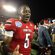Louisville Cardinals quarterback Teddy Bridgewater (5) celebrates after the NCAA Football Russell Athletic Bowl football game between the Louisville Cardinals and the Miami Hurricanes, at the Florida Citrus Bowl on Saturday, December 28, 2013 in Orlando, Florida. Louisville won the game by a score of 36-9. (AP Photo/Alex Menendez)
