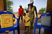 A health worker carries leads a child to a classroom to vaccinate her during a national polio immunization exercise at the Moglaa primary school in the town of Moglaa, northern Ghana on Friday March 27, 2009.