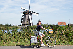 Young woman delivering mail on bicycle for Postnl with windmill to rear at Kinderdijk UNESCO World Heritage Site in The Netherlands