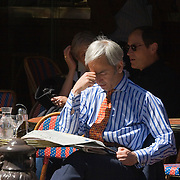 Businessman sitting alone at table reading newspaper at Le Bonaparte cafe in St-Germain-des-Pres, Paris, France<br />