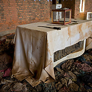 Bloodstained altar, with maschete, ethnicity ID papers and victims' clothing, Nyamata Church memorial