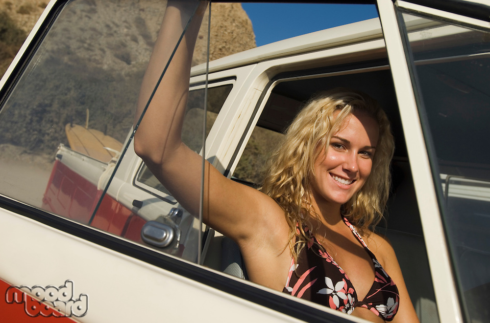 Pretty Young Woman in Car at Beach