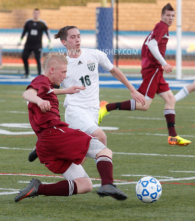 Fort Ann's Seth Godfrey, left, kicks the ball away from Hayden Guay (16) of Chazy during the Class D state semifinals at Faller Field in Middletown on Saturday. Nov. 16, 2013. (Tom Bushey – Special to The Post-Star)