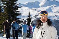 A group of women, 40-50, take a break from skiing and snowboarding Blackcomb Mountain on a sunny winter day. Whistler Peak rises behind. Whistler, BC Canada.
