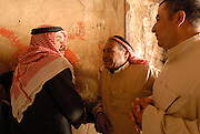 Three men talk right outside an oven while queueing for bread in Syria