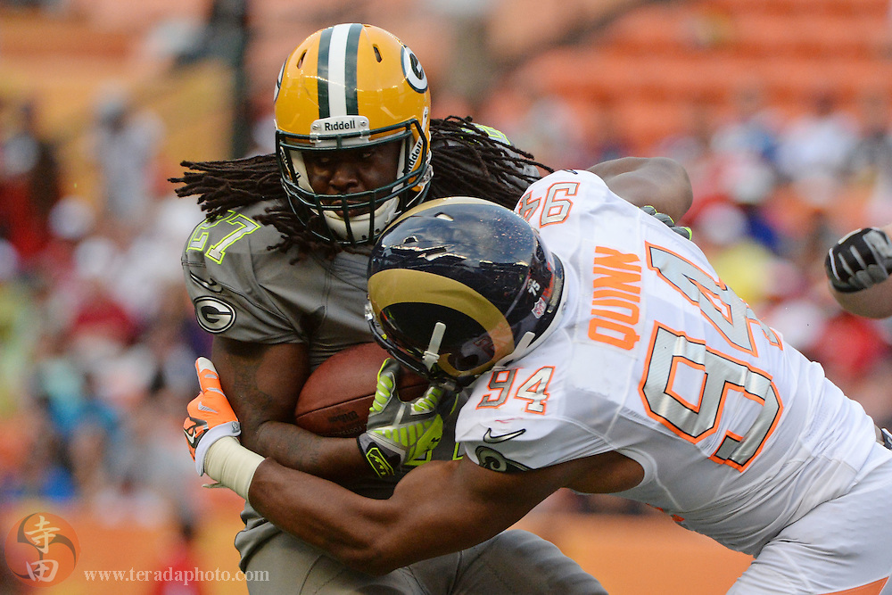 January 26, 2014; Honolulu, HI, USA; Team Sanders running back Eddie Lacy of the Green Bay Packers (27) is tackled by Team Rice defensive end Robert Quinn of the St. Louis Rams (94) during the fourth quarter of the 2014 Pro Bowl at Aloha Stadium. Team Rice defeated Team Sanders 22-21.