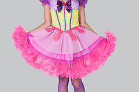 Midsection of young woman in doll's costume standing against gray background