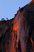 "Horsetail Fall, an ephemeral waterfall that plunges from the top of El Capitan in Yosemite National Park, California, is reddened by the setting sun. The waterfall, which flows only for a few weeks each year in late winter and early spring, drops a total of 2,130 feet (650 meters). Horsetail Fall is best known for its dramatic ""fire fall"" effect, which if the weather and water supply conditions are just right, occurs each year in late February when the setting sun directly lights up the waterfall."