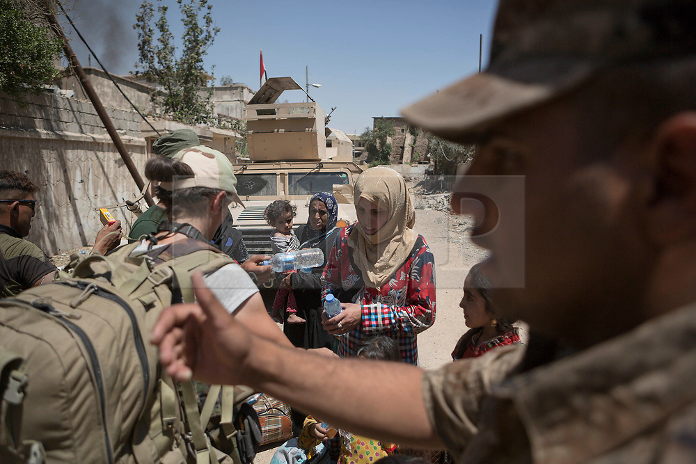 © Licensed to London News Pictures. 15/06/2017. Mosul, Iraq. Iraqi Soldiers of the 9th Armoured Division hand out food and water to recently escaped civilians who are fleeing from ISIS held West Mosul.<br /> <br /> Despite heavy fighting between the Islamic State and Iraqi Security Forces many civilians have started to leave ISIS territory in West Mosul. Mosul residents, many of whom have been in hiding in their homes since the start of the West Mosul Offensive, often have to run through ISIS sniper and machine gun fire to reach the safety of Iraqi Security Forces positions. Photo credit: Matt Cetti-Roberts/LNP