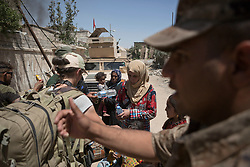 &copy; Licensed to London News Pictures. 15/06/2017. Mosul, Iraq. Iraqi Soldiers of the 9th Armoured Division hand out food and water to recently escaped civilians who are fleeing from ISIS held West Mosul.<br /> <br /> Despite heavy fighting between the Islamic State and Iraqi Security Forces many civilians have started to leave ISIS territory in West Mosul. Mosul residents, many of whom have been in hiding in their homes since the start of the West Mosul Offensive, often have to run through ISIS sniper and machine gun fire to reach the safety of Iraqi Security Forces positions. Photo credit: Matt Cetti-Roberts/LNP