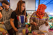 "13 FEBRUARY 2014  - NONTHABURI, NONTHABURI, THAILAND: Thai rice farmers pick up emergency rations donated to the farmers by members of the public at the Ministry of Commerce complex in Nonthaburi, outside of Bangkok. The Thai government instituted a ""rice pledging scheme"" after the election in 2011. The government agreed to buy farmers' rice crops at above market prices then planned to warehouse the rice and sell it on international markets when prices recovered. At the same time, India and Vietnam started to export large quantities of rice and the Thai government fell short of funds to pay for rice it had already purchased from farmers. Many farmers have not been paid for rice grown in 2013 and some of the rice in the Thai warehouses is allegedly rotting. Thailand has fallen from number 1 rice exporter in the world to number 3 and several government to government contracts the Thais signed with rice importing countries (like China) have been cancelled. Farmers, once key supporters of the government are now joining anti-government protests in Bangkok and occupying government ministries including the Ministry of Commerce.    PHOTO BY JACK KURTZ"