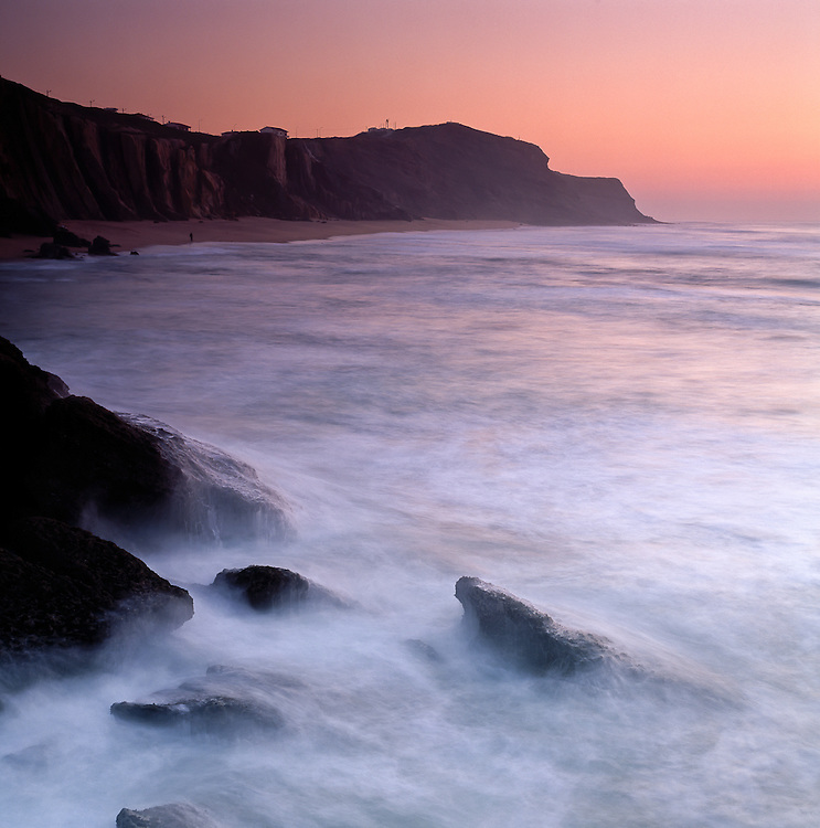 The cliffsides bordering the beaches at Santa Cruz welcome the waves rolling in during yet another end of day.