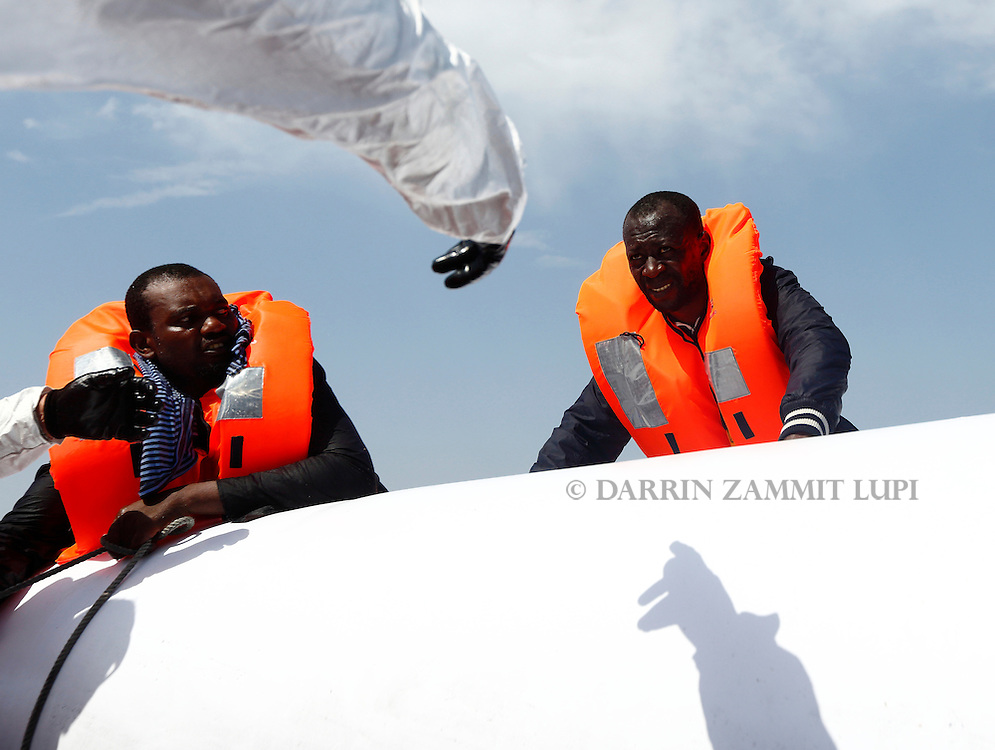 A Migrant Offshore Aid Station (MOAS) rescuer from the MOAS ship MV Phoenix reaches out to a migrant on a rubber dinghy some 20 miles (32 kilometres) off the coast of Libya, August 3, 2015.  118 migrants were rescued from a rubber dinghy off Libya on Monday morning . The Phoenix, manned by personnel from international non-governmental organisations Medecins san Frontiere (MSF) and MOAS, is the first privately funded vessel to operate in the Mediterranean.  Picture taken August 3, 2015.<br /> REUTERS/Darrin Zammit Lupi <br /> MALTA OUT. NO COMMERCIAL OR EDITORIAL SALES IN MALTA