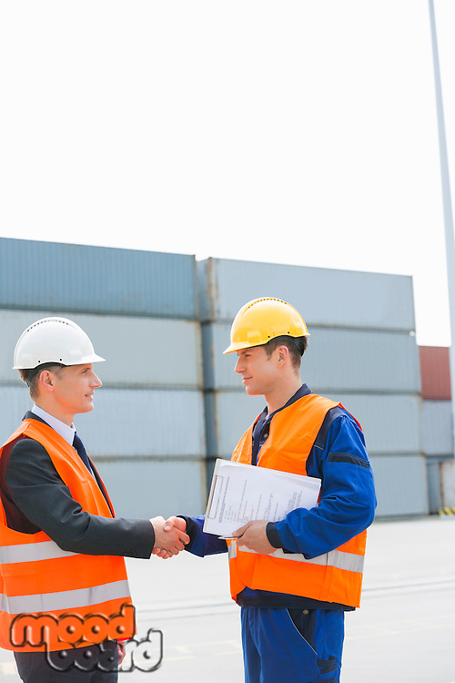 Side view of workers shaking hands in shipping yard