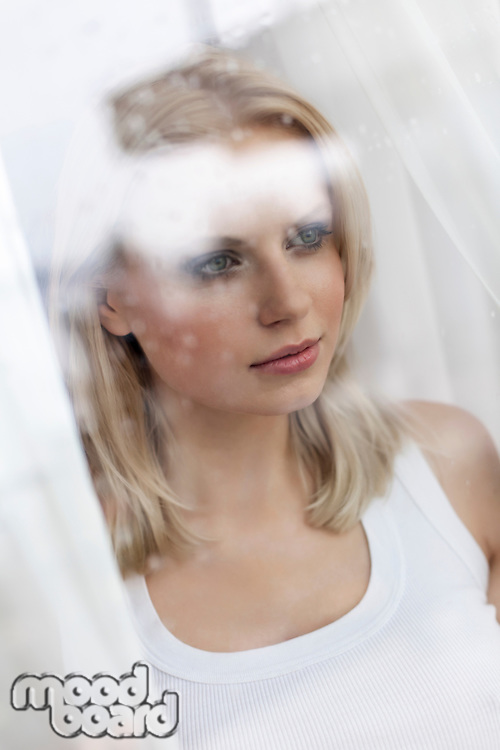 Beautiful young woman looking through hotel window