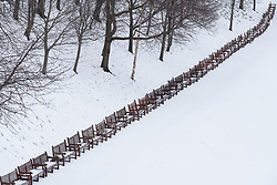View over closed Princes Street Gardens with row of empty park benches after heavy snow with snow pristine in Edinburgh, Scotland, United Kingdom