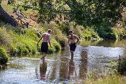 © Licensed to London News Pictures. 23/06/2020. London, UK. Two men cool off in the Beverley Brook in Richmond Park in South West London as as forecasters predict a hot week ahead with temperatures expected to reach over 30c. Prime Minister, Boris Johnson announces that tourism and hospitality including pubs, restaurants and campsites can now reopen from the 4th of July as well as reducing the 2 metre rule to 1 metre.  Photo credit: Alex Lentati/LNP