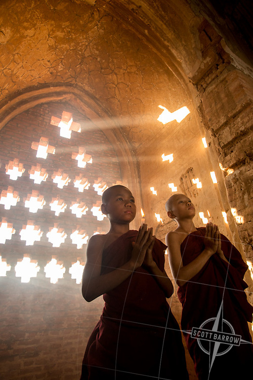 Young monk (s) praying with candles in a temple or monastery.