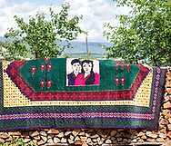 A carpet  edged with a portrait of a married couple. When girl get married she must be virgin that's the couple don't live together after engagement.<br /> Kakheti region, Georgia, 2016.
