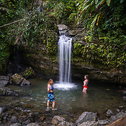 RIO GRANDE, PUERTO RICO -- FEBRUARY 1, 2019: <br /> Lissette Gonz&aacute;lez, 29 in blue, a visitor from San Antonio, Texas, flashes a sign to her friend off camera as visitors to El Yunque National Rain Forest enjoy the waterfall and pond  at the Quebrada Juan Diego (Juan Diego Creek). A few of the rain forest's popular trails and attractions are still not open to the public more that one year after Hurricane Maria's path through Puerto Rico.<br /> (Photo by Angel Valentin)