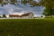 A barn and stable on a rolling hill of green grass as autumn approaches.